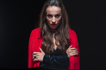 grim vampire woman in red cloak looking at camera isolated on black Stockfoto