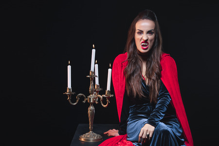 sexy woman in vampire costume sitting near vintage candelabrum isolated on black