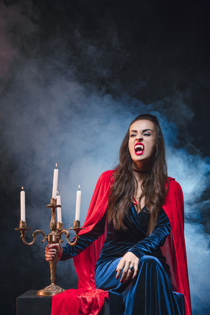 woman in vampire costume holding vintage candelabrum on darkness with smoke