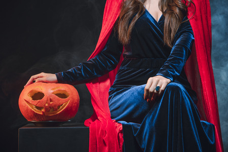 cropped view of woman in red cloak with jack o lantern on darkness with smoke