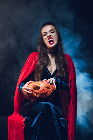 woman in vampire costume holding jack o lantern on darkness with smoke