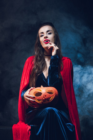 attractive woman in vampire costume holding jack o lantern on darkness with smoke