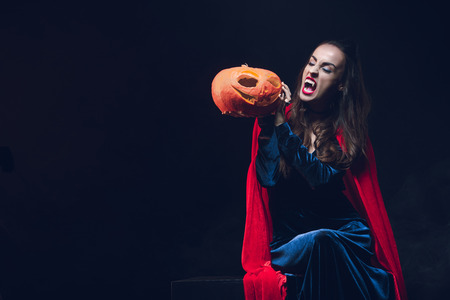 mystery woman in vampire costume holding jack o lantern on dark background Stock Photo