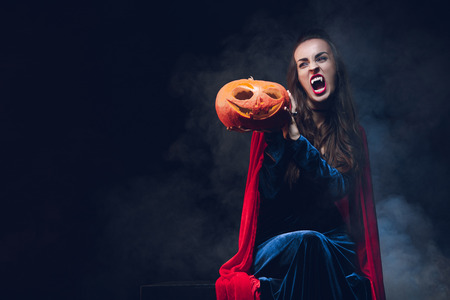 woman in vampire costume holding pumpkin on dark background with smoke Stok Fotoğraf