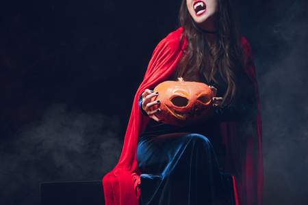 cropped view of beautiful woman in vampire costume holding pumpkin on darkness with smoke Stock Photo
