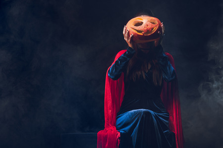 woman in red cloak holding jack o lantern in front of face on darkness with smoke