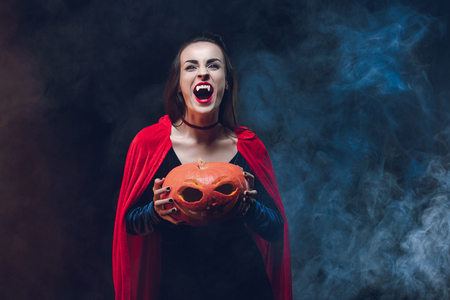 mystic woman in vampire costume holding jack o lantern on dark background with smoke