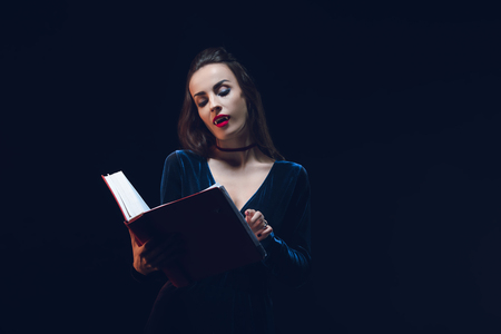 vampire woman reading magic book isolated on black