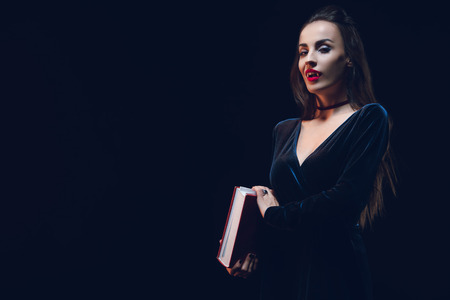 beautiful vampire woman holding magic book isolated on black