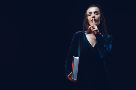 vampire woman showing silence symbol and holding magic book isolated on black