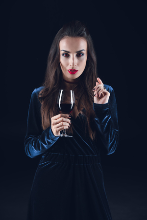 sexy vampire holding wineglass with blood isolated on black