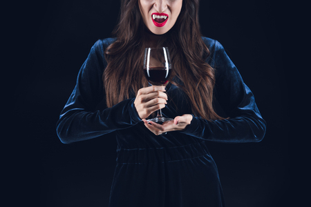 cropped view of vampire holding wineglass with blood isolated on black