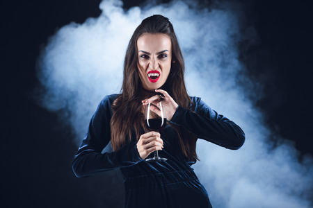 grim vampire holding wineglass with blood on dark background with smoke Stock Photo