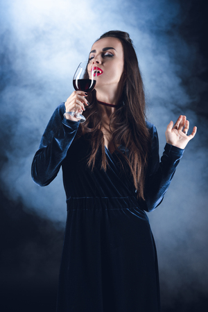vampire drinking blood from wineglass on dark background with smoke