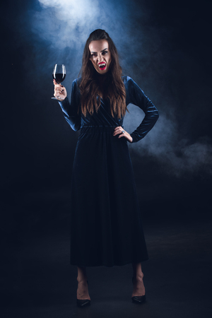 grim vampire holding wineglass with blood on dark background with smoke Zdjęcie Seryjne