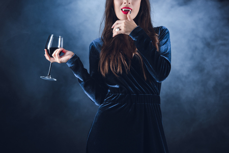 cropped view of vampire holding wineglass with blood and licking her fingers on dark background with smoke