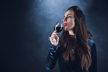 beautiful vampire drinking blood from wineglass on dark background with smoke
