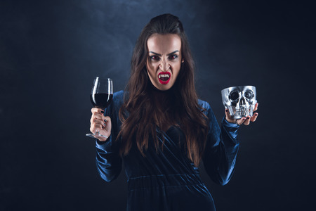 vampire holding metal skull and wineglass with blood on darkness with smoke Stock Photo