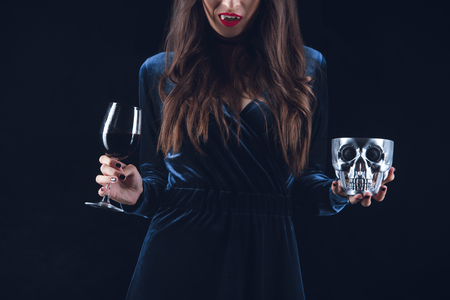 cropped view of vampire woman holding skull and wineglass with blood isolated on black