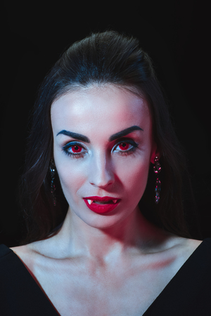 sexy vampire woman with red eyes looking at camera isolated on black