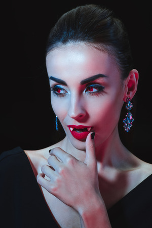 attractive vampire touching her lips isolated on black Stock Photo