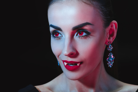 sexy vampire woman showing her teeth isolated on black Stock Photo