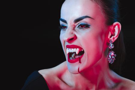 Vampir zeigt ihre Reißzähne und schaut isoliert auf Schwarz weg