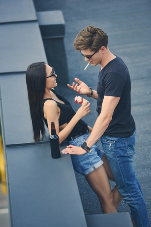 hot multiethnic couple with cigarettes and bottle of beer spending time on roof