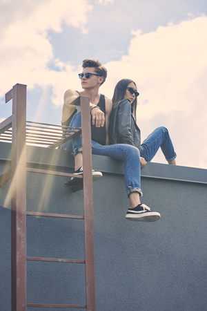 stylish multiethnic couple in sunglasses sitting on roof with sunlight Zdjęcie Seryjne