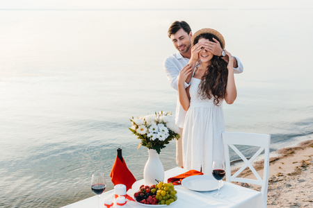 happy man closing eyes and making surprise for girlfriend, romantic date near sea 스톡 콘텐츠