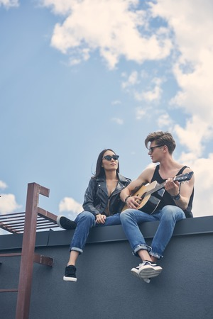 handsome guitarist playing for his asian girlfriend while couple sitting on roof