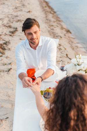 handsome man wearing ring on womans finger after propose on romantic date