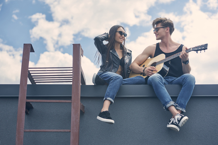 handsome guitarist playing for his asian girlfriend on roof