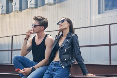 young stylish man smoking cigarette near his beautiful girlfriend in sunglasses