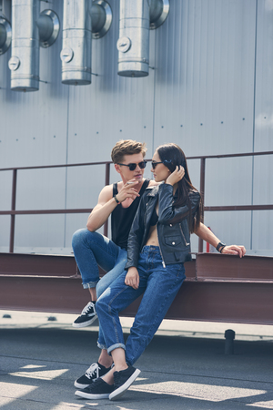 stylish multicultural couple smoking cigarette together