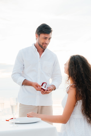 handsome man making propose with ring to girlfriend in romantic date