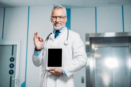 smiling mature male doctor with stethoscope over neck doing ok gesture and showing digital tablet with blank screen in hospital Banco de Imagens