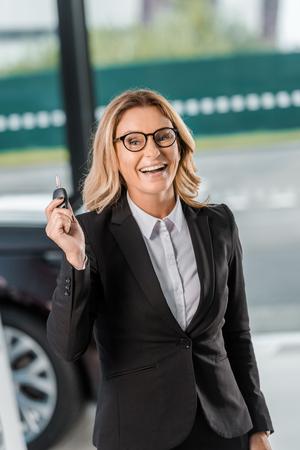 smiling businesswoman holding car key at showroom 免版税图像