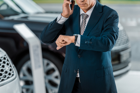 cropped shot of adult businessman talking by phone at car dealership salon and looking at wrist watch