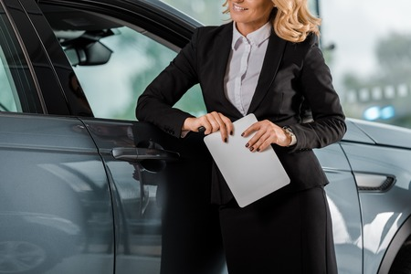 cropped shot of female car dealer with tablet leaning on car in showroom