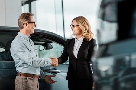Adult customer and female car dealer shaking hands at showroom