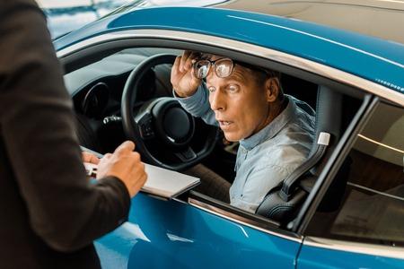 Ausgeschnittene Aufnahme einer Autohändlerin, die einem schockierten Mann im Ausstellungsraum einen Autohausvertrag zeigt