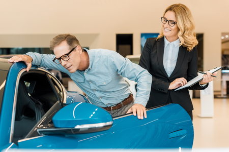 adult man checking luxury sport car with female car dealer at showroom