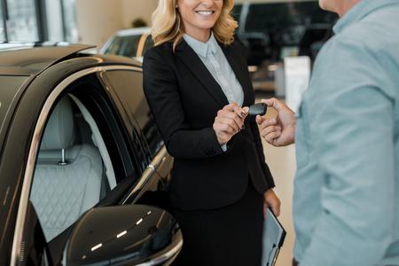 cropped shot of man taking car key from female car dealer at showroom Banco de Imagens