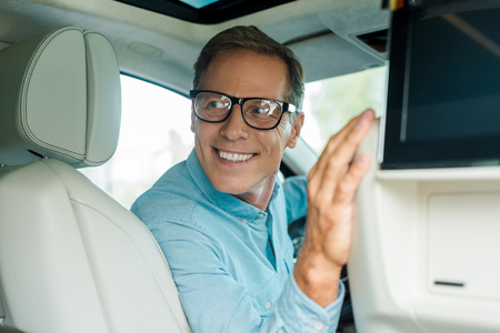 smiling adult man driving luxury car and looking back