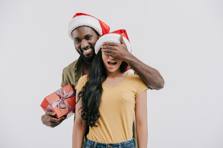 african american boyfriend closing girlfriend eyes and holding new year present isolated on white Stock fotó