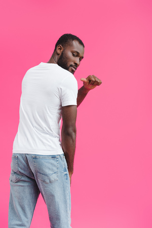 back view of african american man pointing at blank white shirt isolated on pink Stock Photo