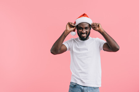 smiling african american man putting on christmas hat isolated on pink background