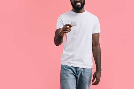 partial view of young african american man with condom isolated on pink background