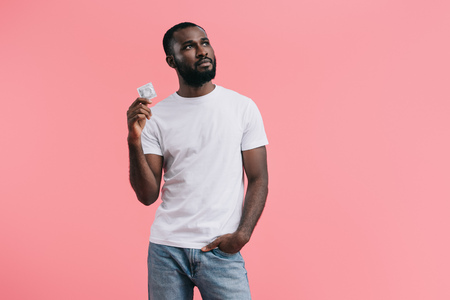 young african american man with condom looking away isolated on pink background Banque d'images